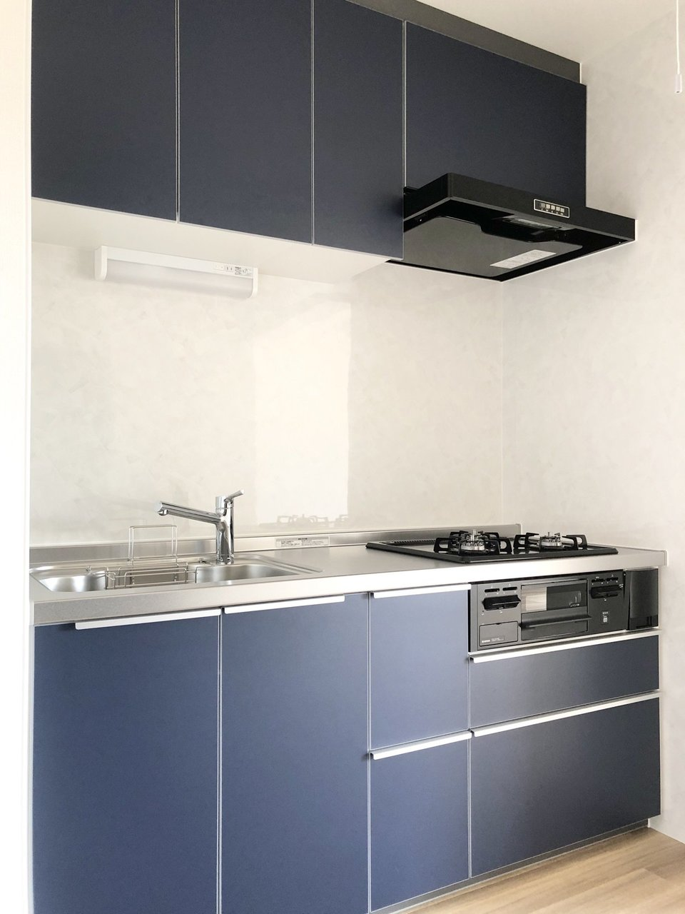 キッチンも上品なネイビーカラーのシステムキッチン。広々としていて収納スペースも豊富。料理が捗りそうです。背面もゆったりとしたスペースが確保されています。