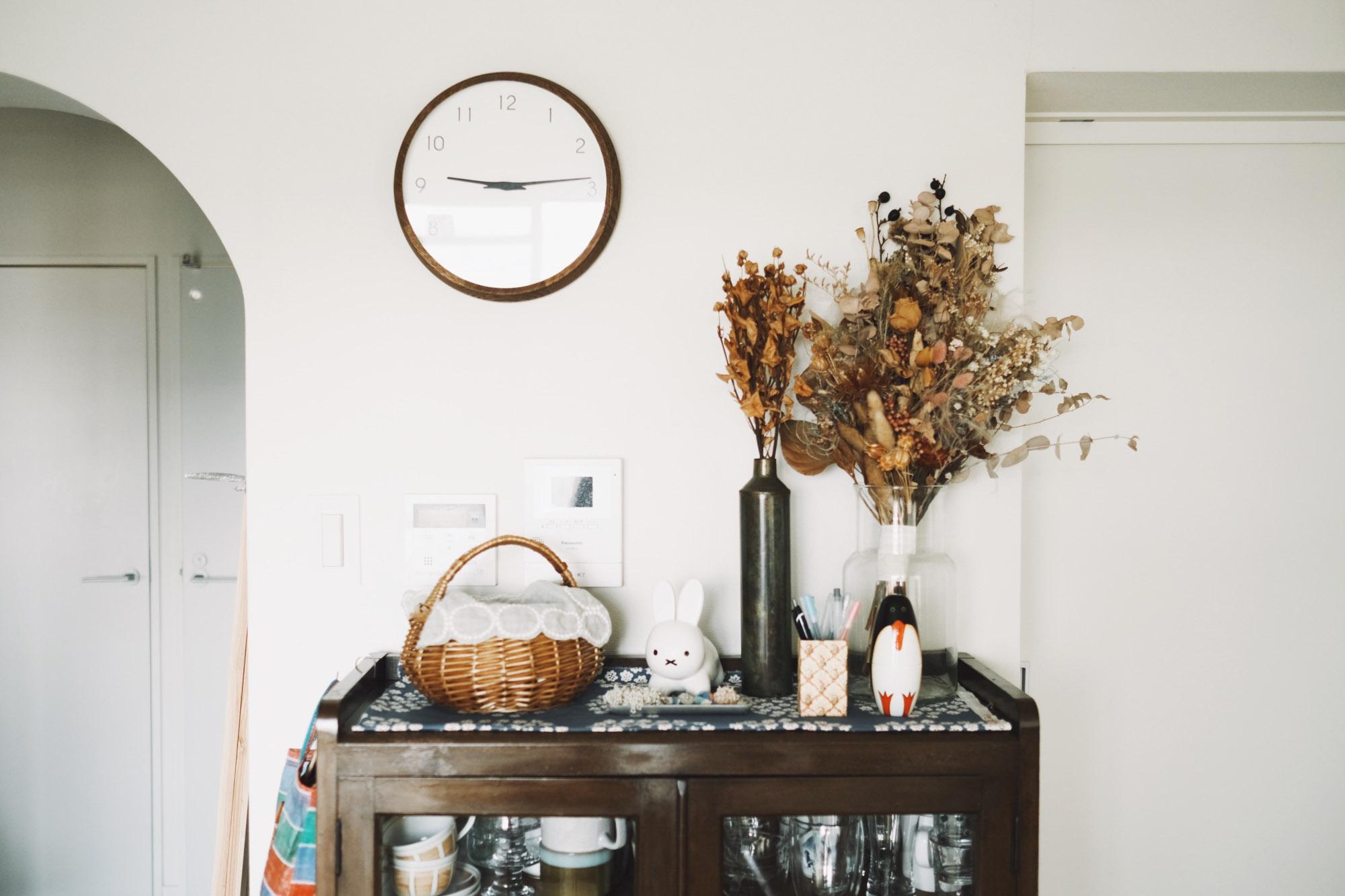 木製の食器棚の上に、カゴ素材やドライフラワーで質感を統一した事例。ボリュームのあるお花で高低差を出しています。かわいらしいキャラクター雑貨や結婚式で使用したお花など。とにかく自分の好きなものを置くことも大切!(このお部屋をもっと見る)