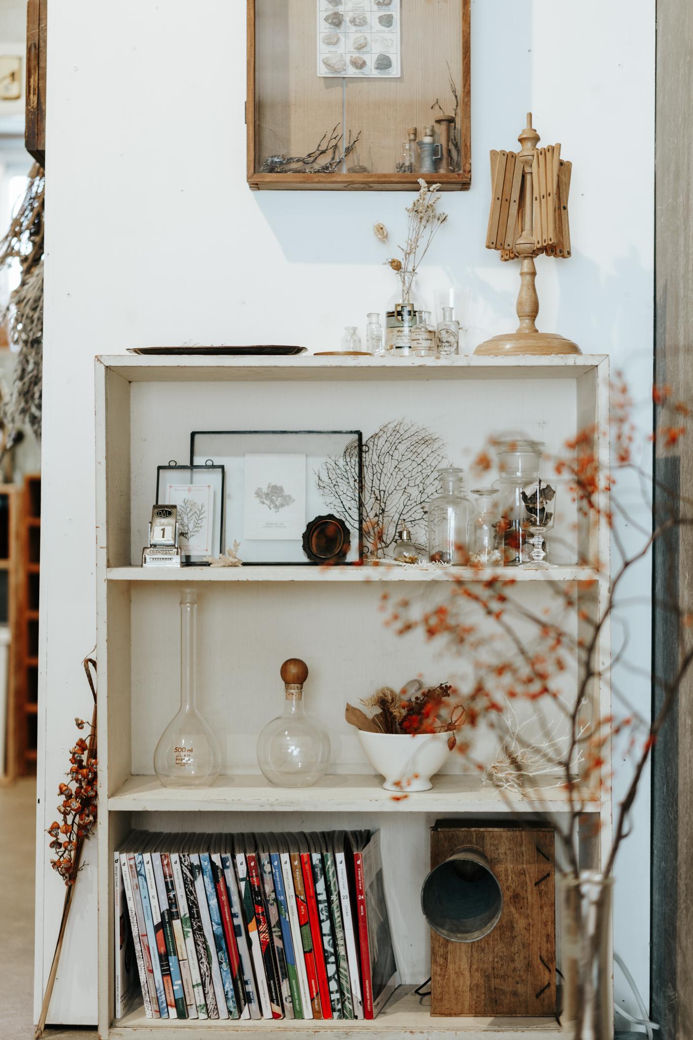 コンクリート打ちっぱなしのワンルームの中に、白のアンティーク棚を設置。下段に色味や大きさが統一された書籍、上段から中段にかけてはディスプレイ、と実用性とおしゃれさを兼ね備えた飾り棚。(このお部屋をもっと見る)