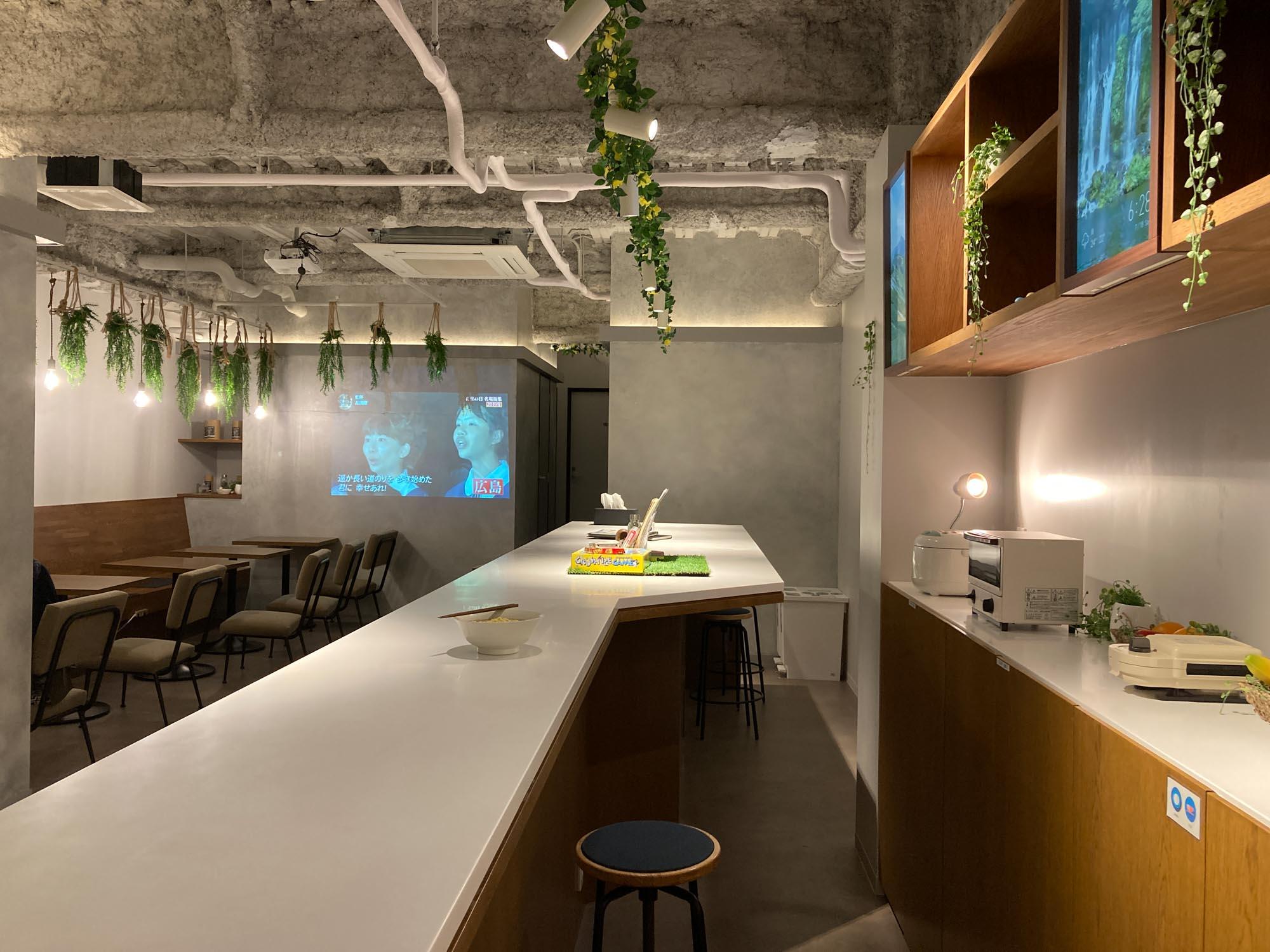 キッチン、カウンター、電源も使えるテーブル席とテレビがあって、宿泊者同士の交流も楽しめるスペースです。