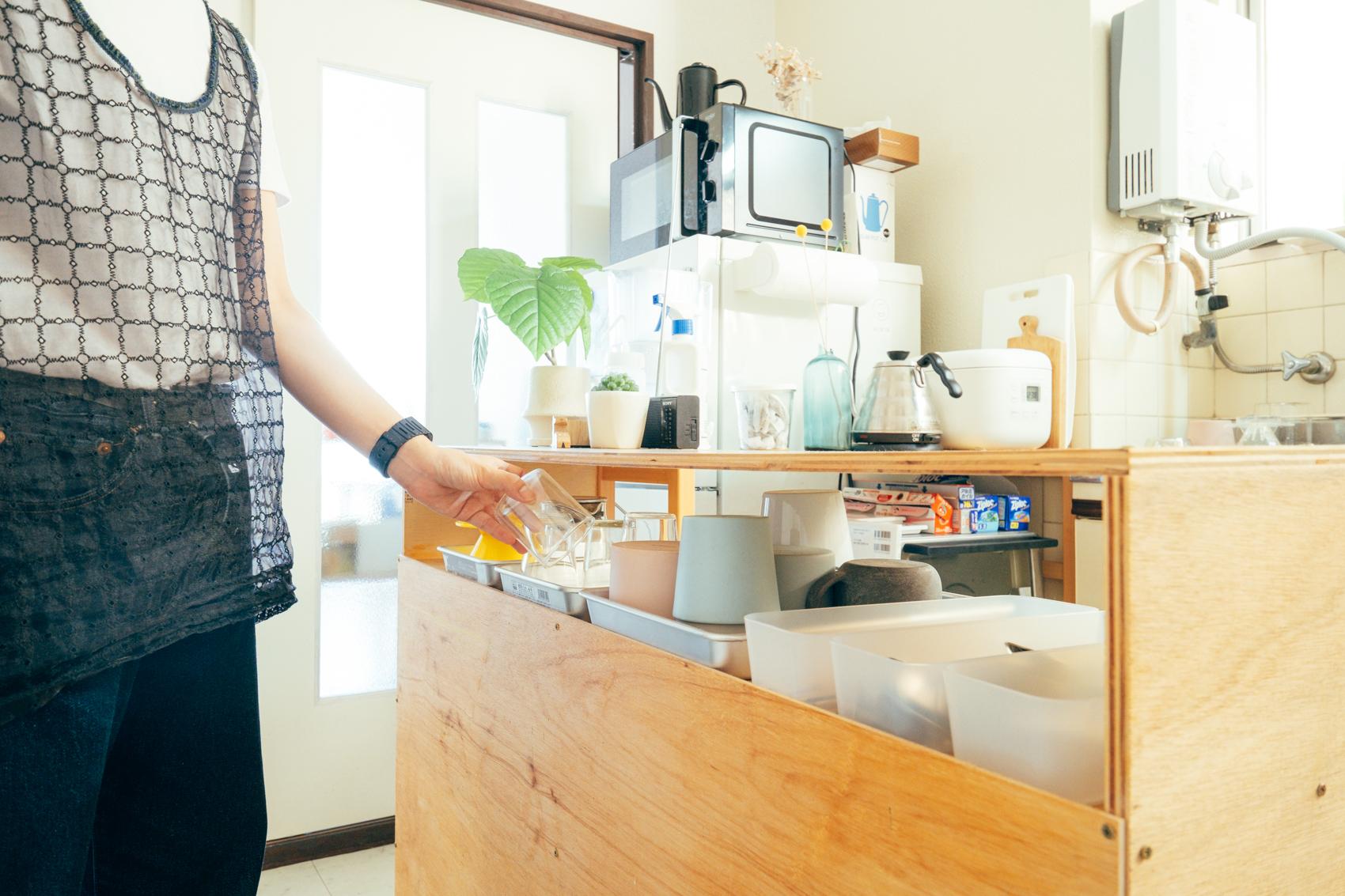 DIYで作った棚には通し窓がついており、これによって、キッチンの内外両方から使用頻度の高いマグなどは取り出しが可能な作りに。 「飲食店に勤めていた時の経験を活かして、通し窓やトレイの落下を防ぐように小さな段差を作っています。」