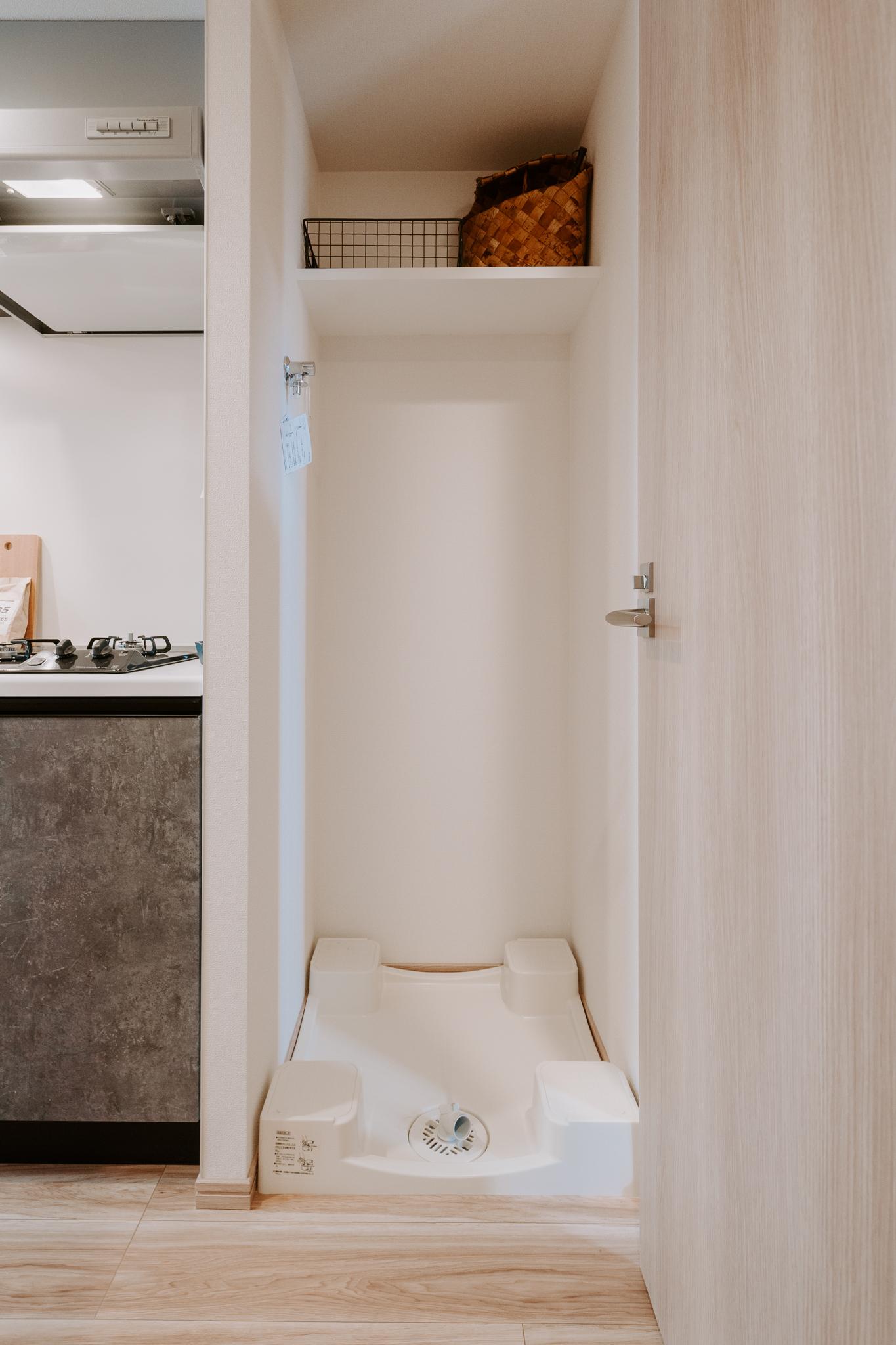 廊下にある洗濯機置き場。上段の棚や壁をうまく使って、タオルや洗剤などを収納できそうです