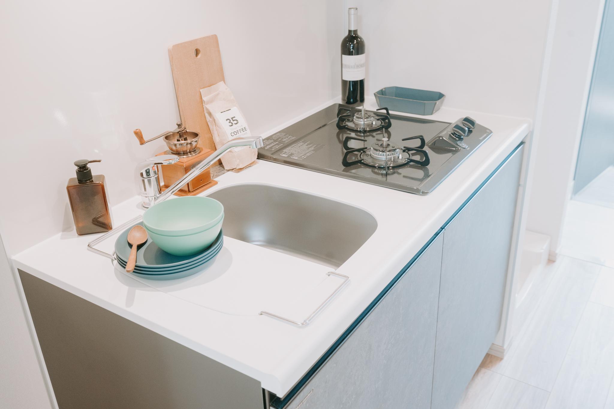 キッチンは二口ガスコンロ付き。調理スペースは狭いのですが、シンクにかけられるプレートがまな板置きに役立ちそうで、特に不便は感じなさそう。