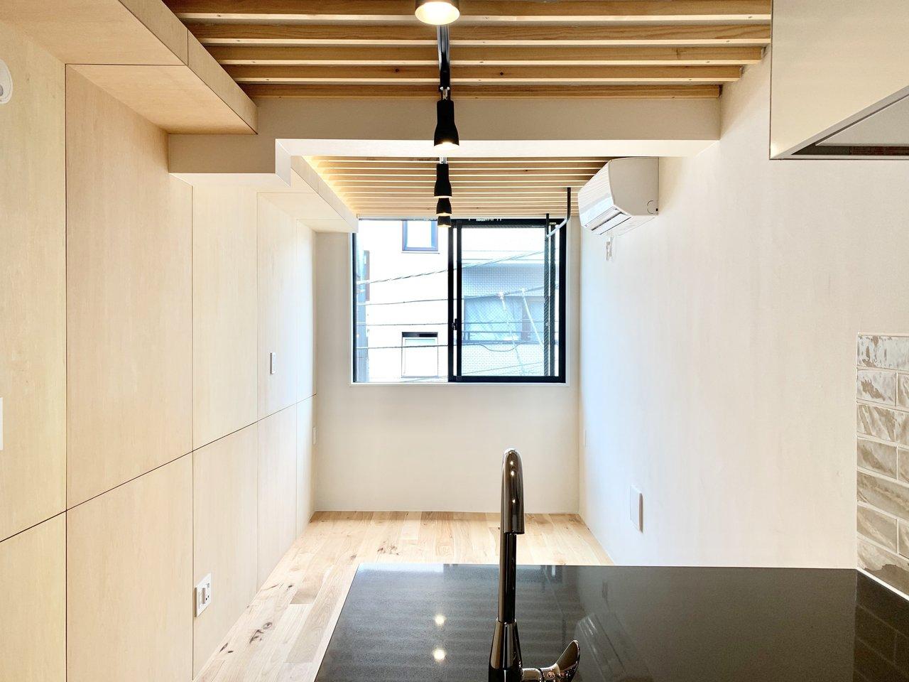 キッチンから見ると、窓が見えますね。無垢床や木目の見える壁を使用していて、シンプルだけど、どこか手触り感のある、あったかい感じのお部屋です。