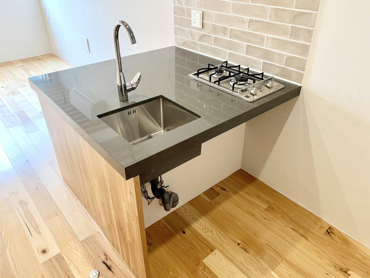 キッチンは二口ガスコンロつき。背面には収納スペースもあるので、食器や調理器具を置くのにも困らなそう。