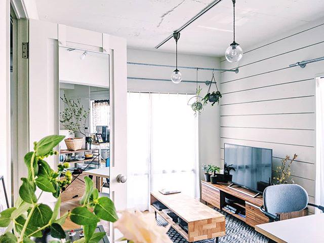 無垢フローリングに、白色の板壁、シルバーのカーテンレールなど、ディテールもさりげなく気が利いているリノベーションのお部屋。ざっくりとした木の家具を合わせて、良い雰囲気で住みこなしていらっしゃいます。丸いライトは FLYMEe で購入。
