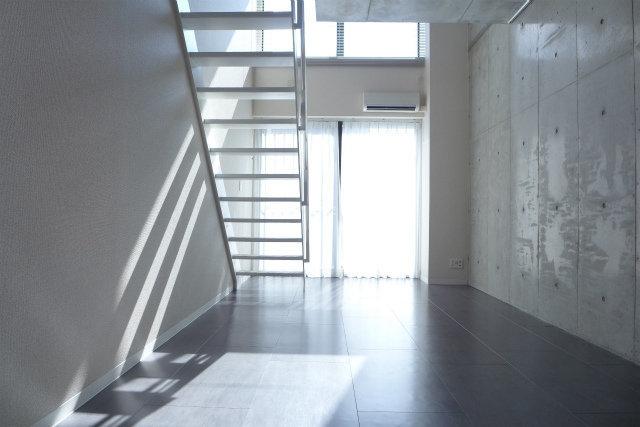 コンクリ打ちっぱなしの壁に包まれた、メゾネットタイプのお部屋。リビングは12畳あり、天井も高く、窓も高く。開放的な空間が広がります。