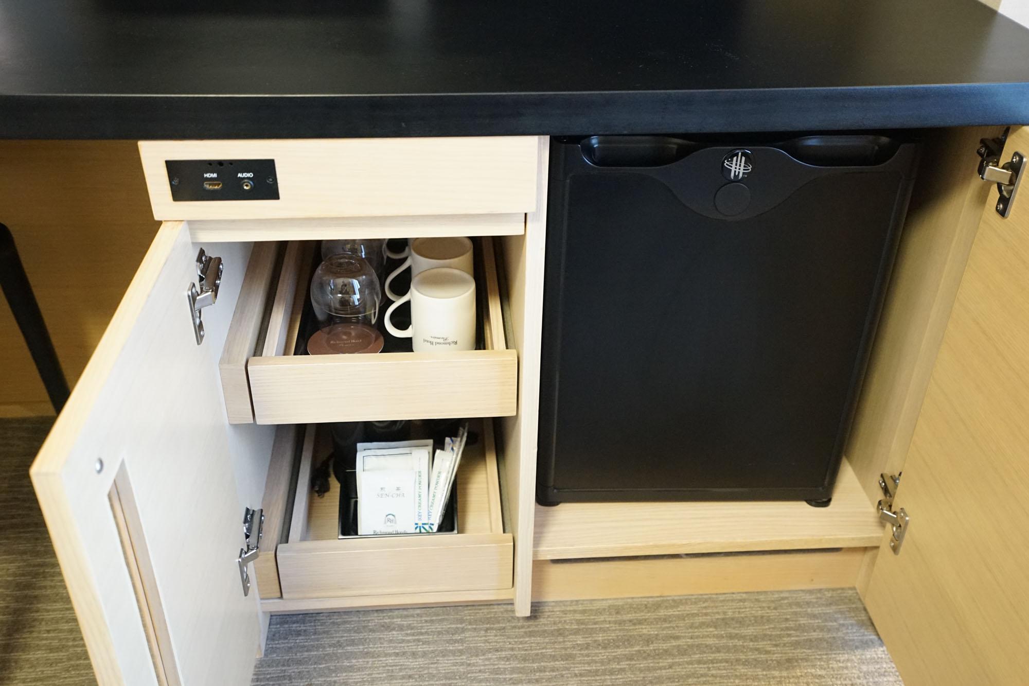 テレビ下にはミニ冷蔵庫に、もちろん電気ポットも。しまっておく場所があるのでデスクの上がすっきりしてありがたいですね。