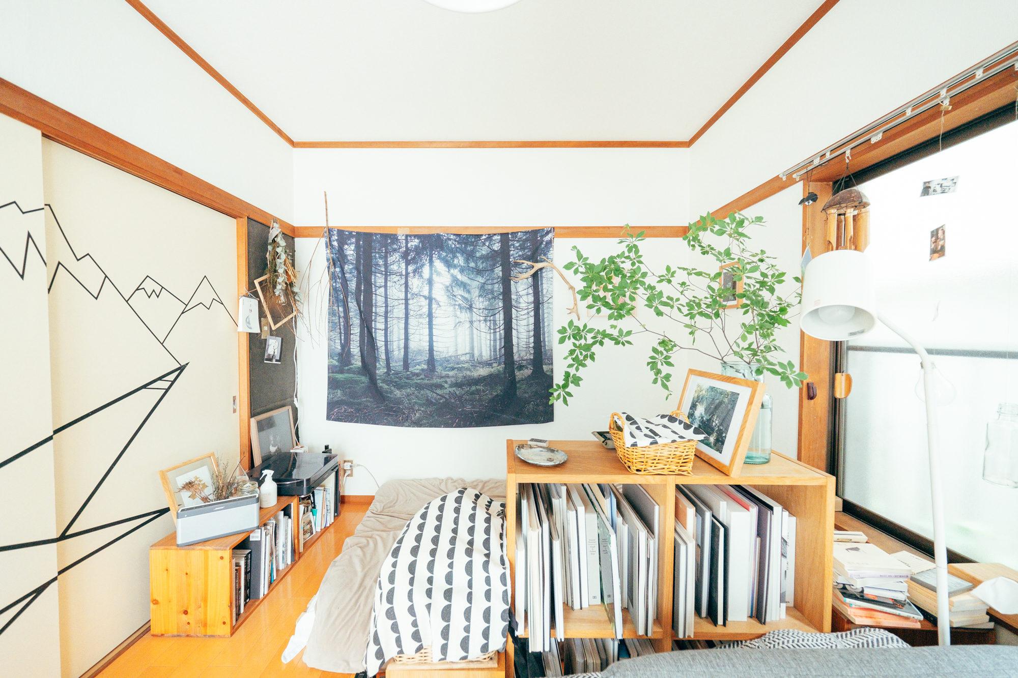 空間が空いて少し寂しい場所には、布を飾るのもおすすめ。こちらのお部屋では、大きなタペストリーをかけています。林の柄が、部屋に奥行きを持たせてくれているように感じますね。(このお部屋をもっと見る)