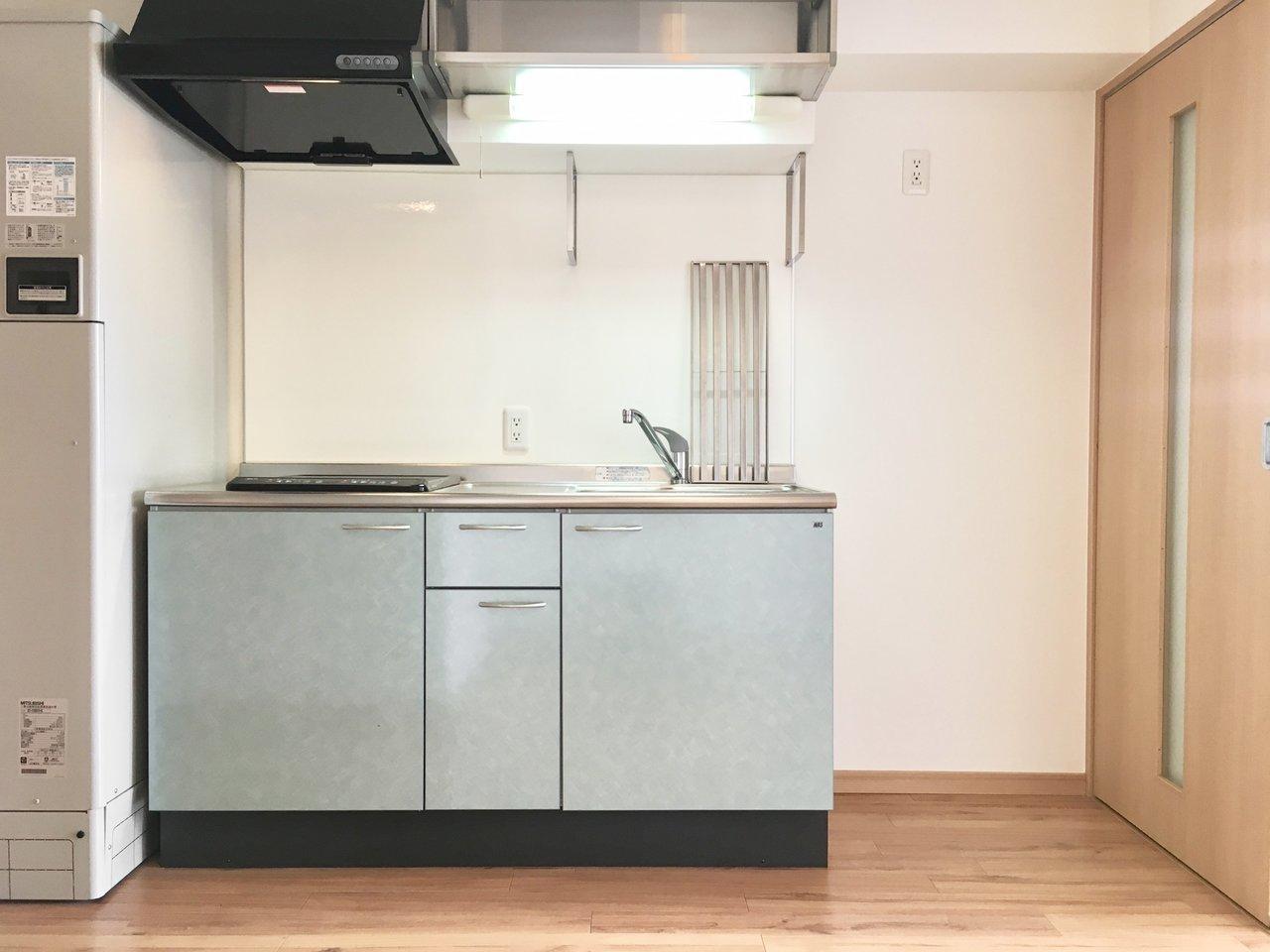 キッチンは淡いブルー色。掃除がしやすいIHコンロが二口ついています。