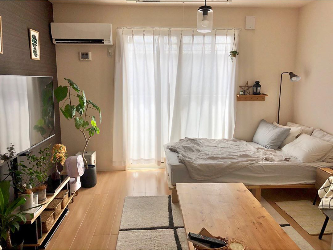 ベッドとソファ、そして広めのコーヒーテーブルをおいてもゆとりある室内。 「何度も模様替えをして、最終的にこの配置に落ち着きました。植物に水をあげるため、なるべくベランダに続く動線に物を置かないようにしています」