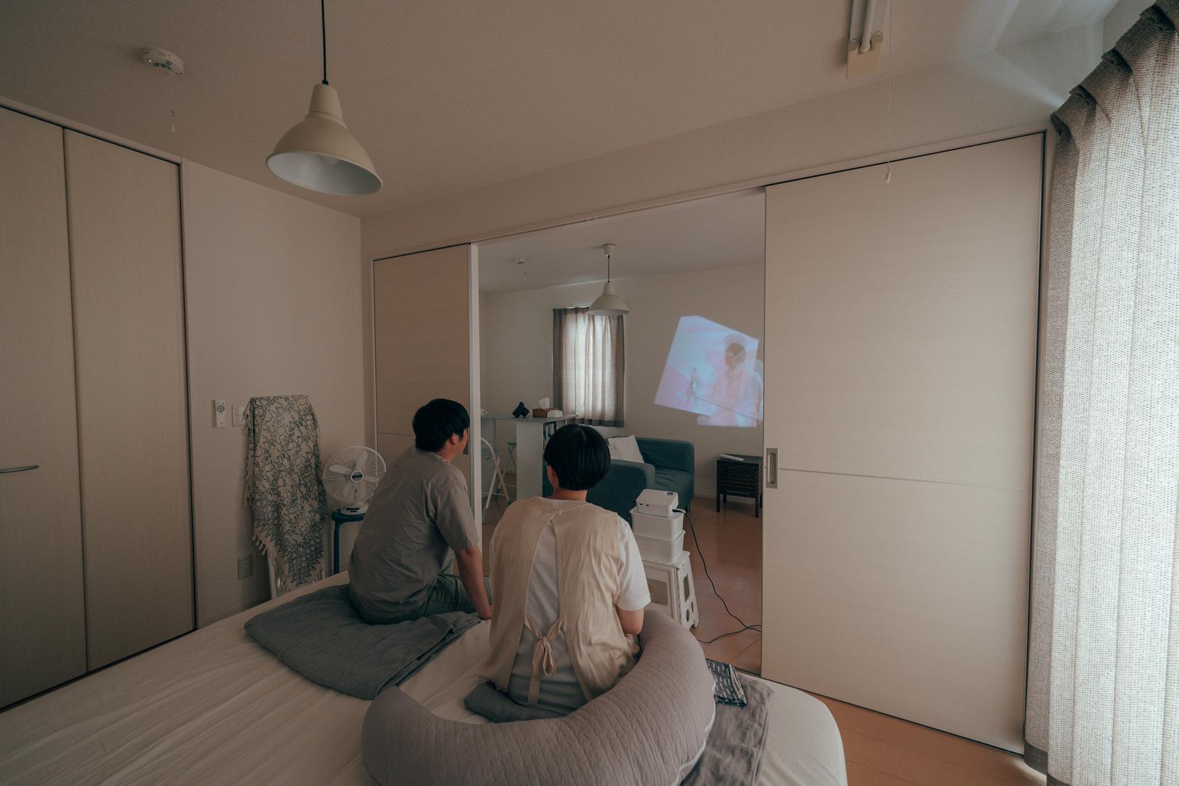 白く、日当たりの良い寝室は夜になると、全く異なる空間に様変わり。 「寝室の向かいにある壁はあえて何も飾らないようにすることで、ホームシアターのような空間を作り上げています。」