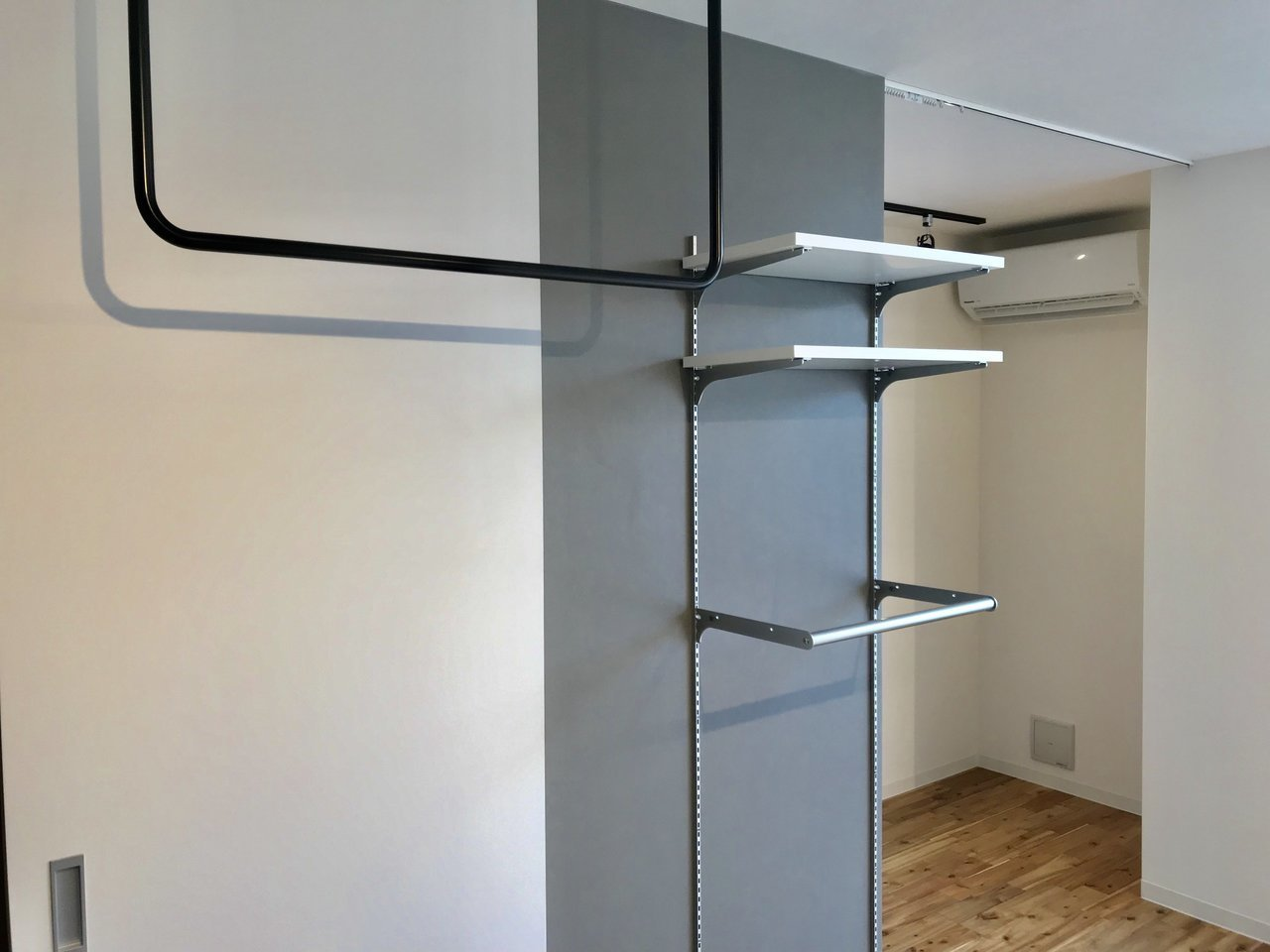 壁には稼働式の棚。天井からはアイアンのハンガーパイプが吊るされていていろいろと使えそう。L字型になった奥の部分には、ベッドを置いたらいいですかね。