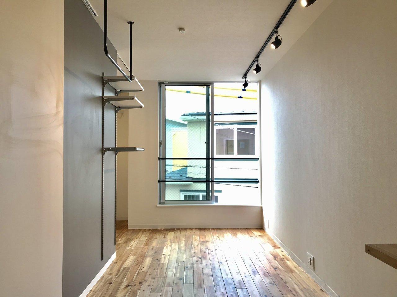 9.27畳の、比較的ゆったりとした造りのワンルーム。濃い色合いのフローリングが、グレーの壁紙によく合います。