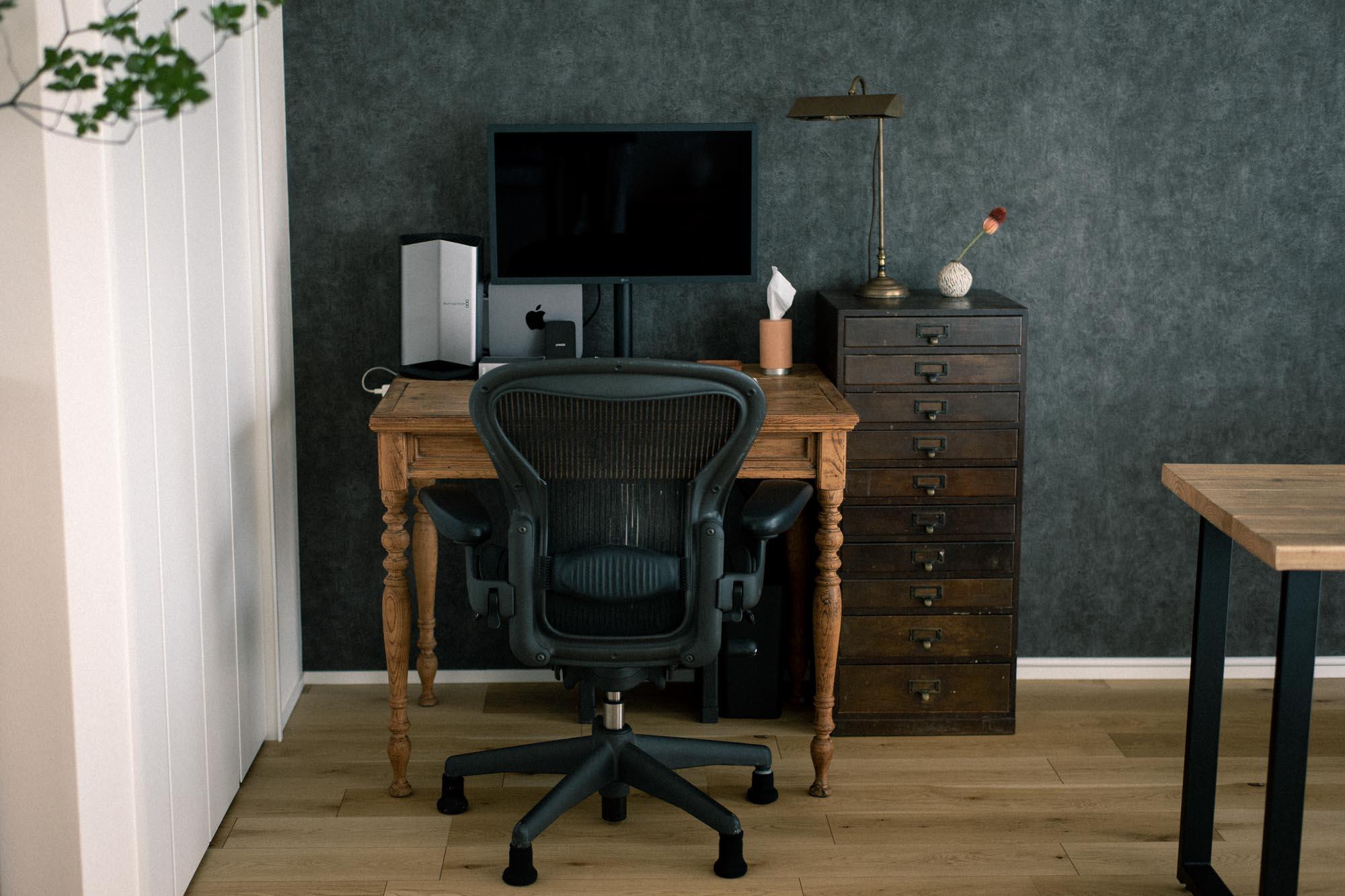 部屋の隅にあるワークデスクはアンティーク。足のデザインも、大量生産の家具ではなかなか味わえない、個性的なデザインになっています。デスクとの雰囲気に合わせて、棚や照明の家具も揃えられていて、机に向かう時間に落ち着きを与えてくれそう。
