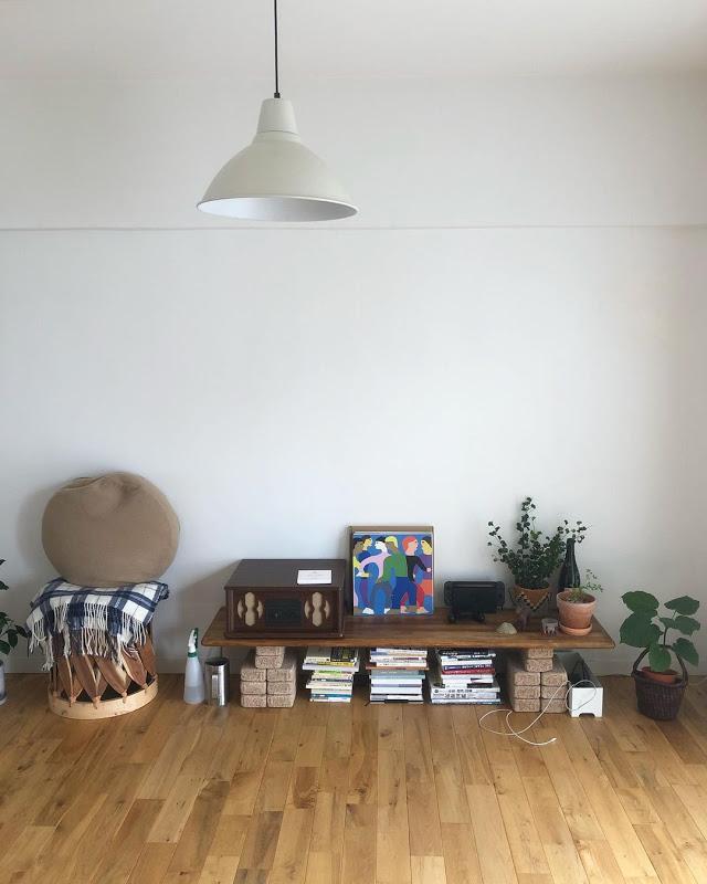 リビングの棚は、ワックスを塗って仕上げた板をブロックの上に載せたもの。圧迫感が出ないよう、低めに配置。上の壁にはプロジェクタで映像を映して楽しみます。左に置かれているスツールは、家具屋さんで見つけたメキシコの椅子。お気に入りで、いつも目に触れる場所に飾って楽しみ、お客さんが来たときにも使います。