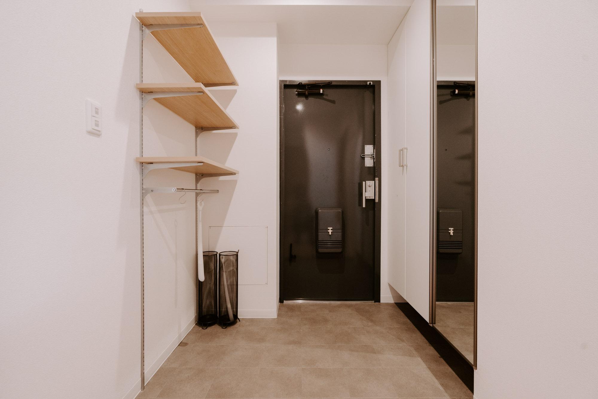 玄関のスペースも広い。大きなシューズクローゼットは姿見つきで、身だしなみチェックも可能。そして吊るせる収納レールをここにも。棚板の位置が動かせるので、下にはベビーカーなどの高さのある物も置けるよう考えられています。