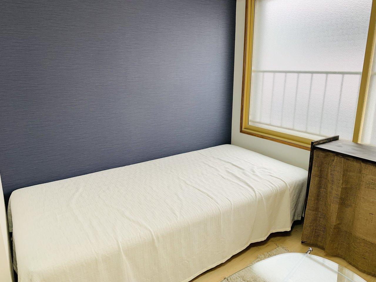 窓際にはシングルベッドがちょうどすっぽり収まるスペースも。ネイビーのアクセントクロスも素敵です。