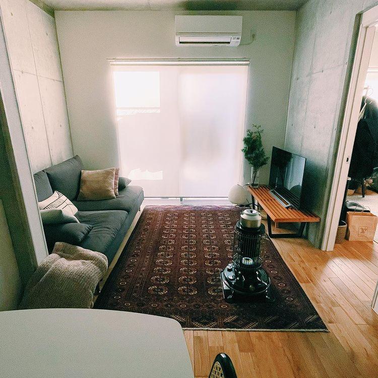 暖色系のラグとアラジンストーブが、打ちっぱなしのお部屋でもうまく暖かな雰囲気を作っています。