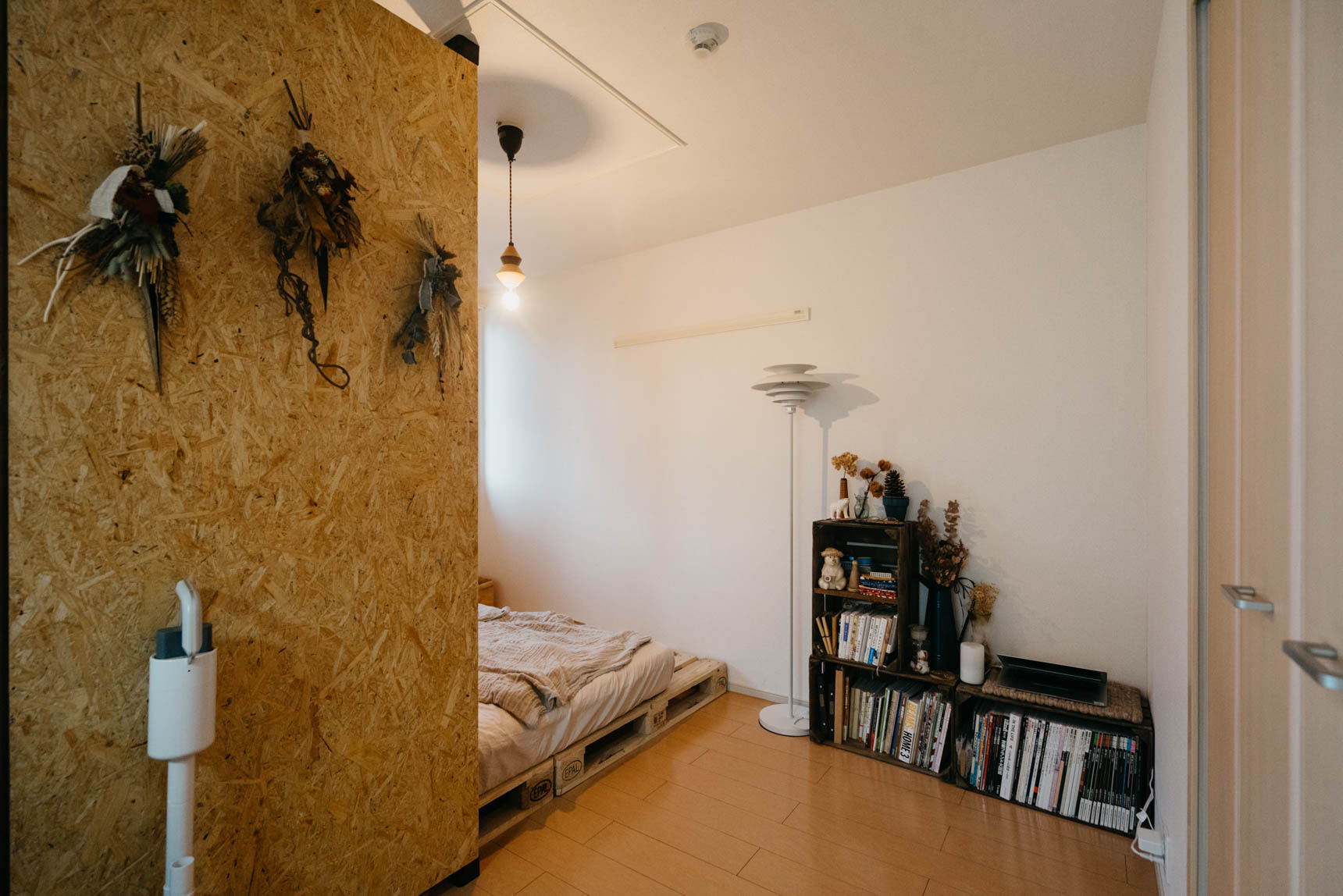 LDK隣の寝室は、引き戸を開けっ放しで使っているため、パーティクルボードを使った間仕切りで目隠しにしています。「ドライフラワーが飾れるように」というのは、Ikumiさんからのリクエスト。