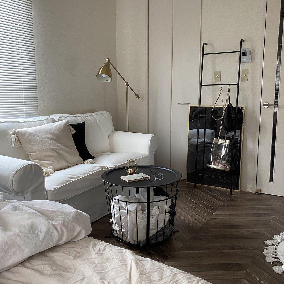 居室の広さは8畳ほど。ヘリンボーン風のフローリングシートは、ご自身で敷いたもの。ベッドをベランダ側に寄せて、手前にソファ、ソファの対面には在宅ワーク用のデスクを配置。