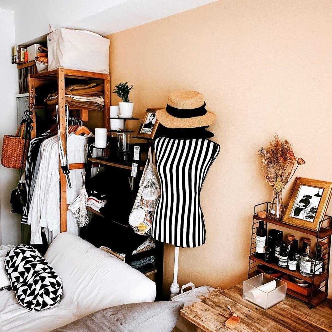 ベッドの反対側にも、木製のハンガーラックを置いて衣類の収納に。ハンガーラックの横のオープンラックには、ショップのように畳んでしまわれています。
