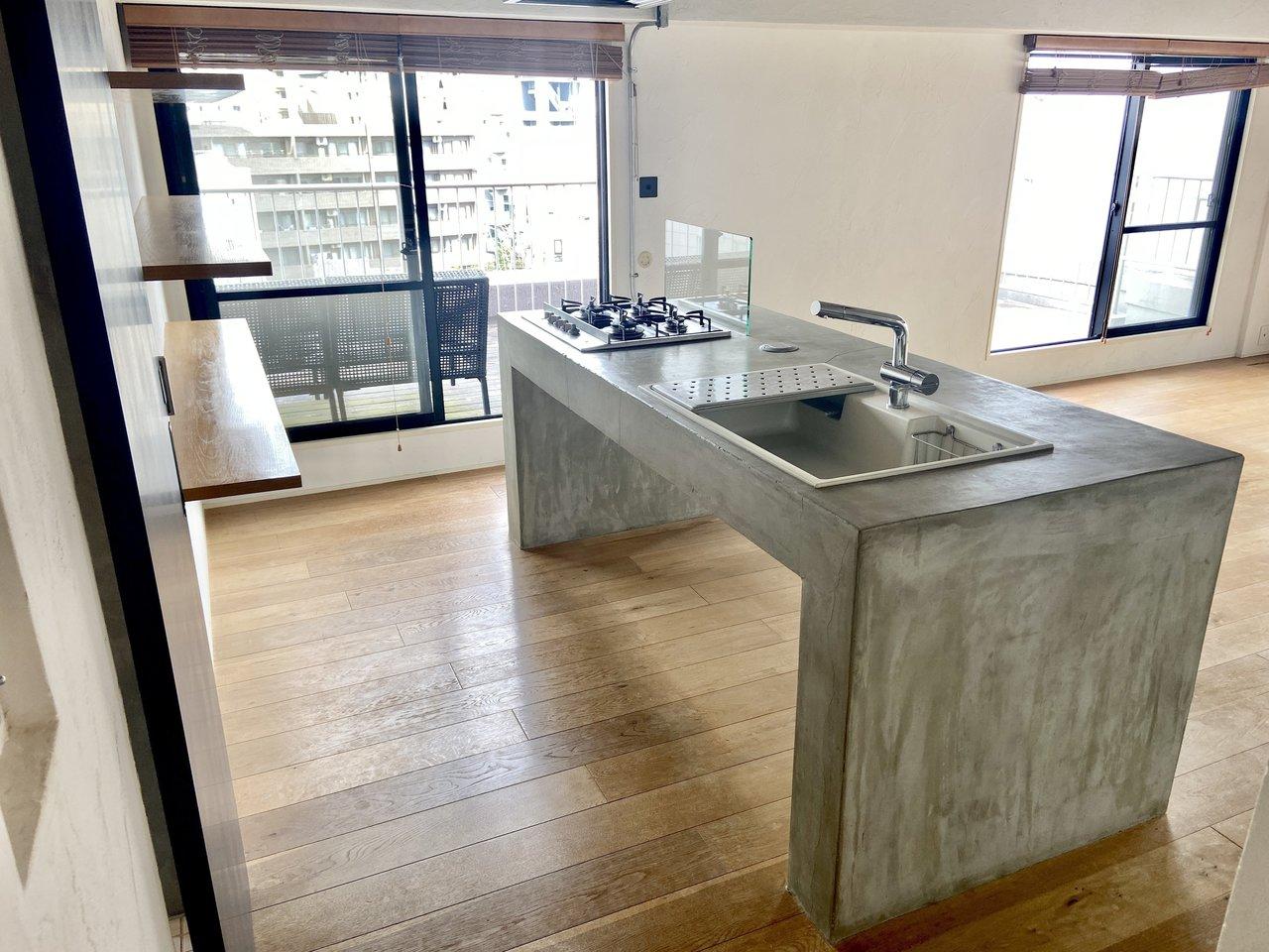 キッチンは4口コンロのアイランドタイプでとてもスタイリッシュ!窓の外にはルーフバルコニーが見えます。