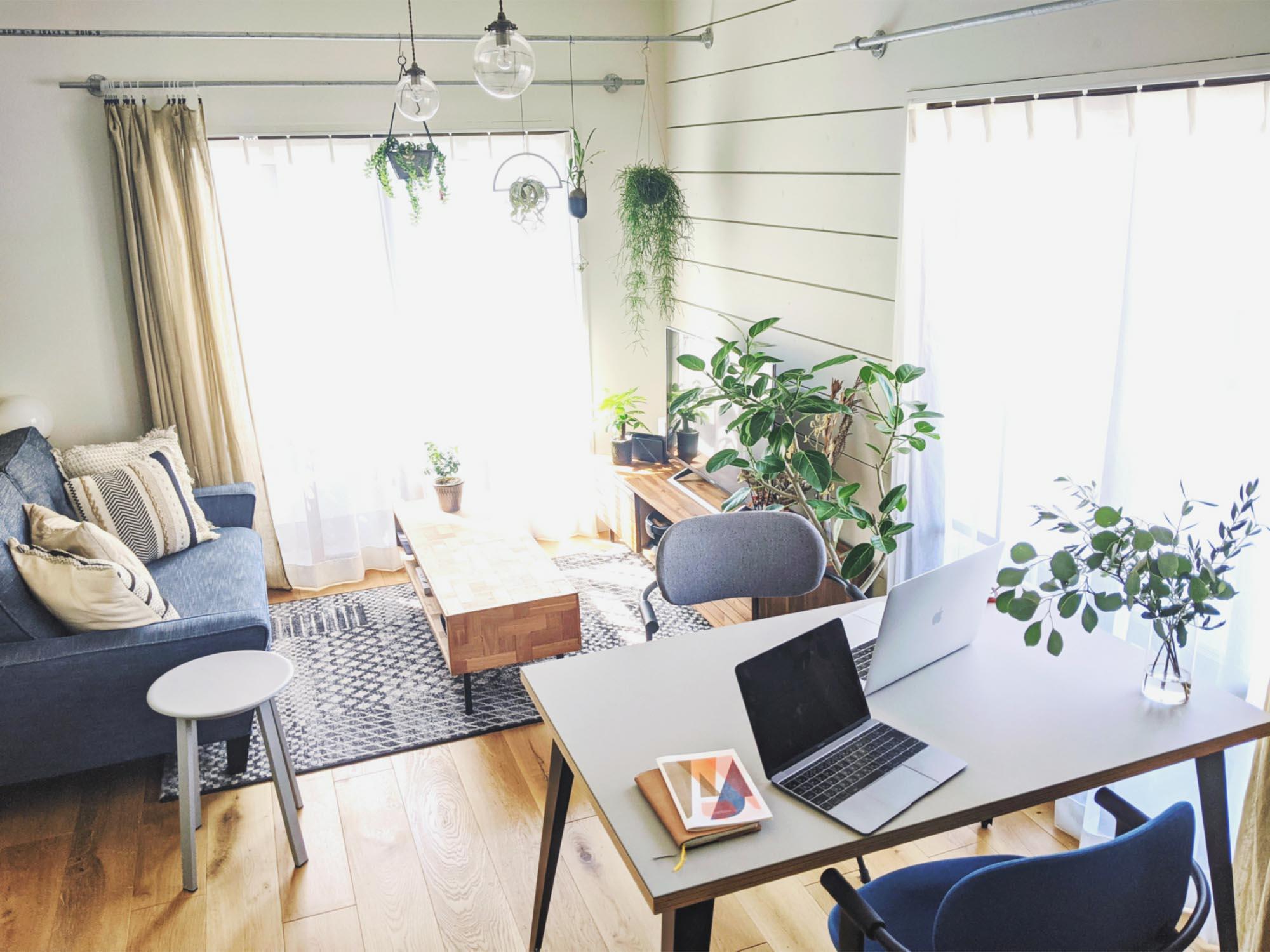 手前にある、ワークデスク兼ダイニングテーブルで過ごすことが多いという、二人暮らしのお部屋。鉢植えや吊るしたもの、ローテーブルに置かれたものなど、たくさんのグリーンが一度に視界に入って、気持ちがいいですね。