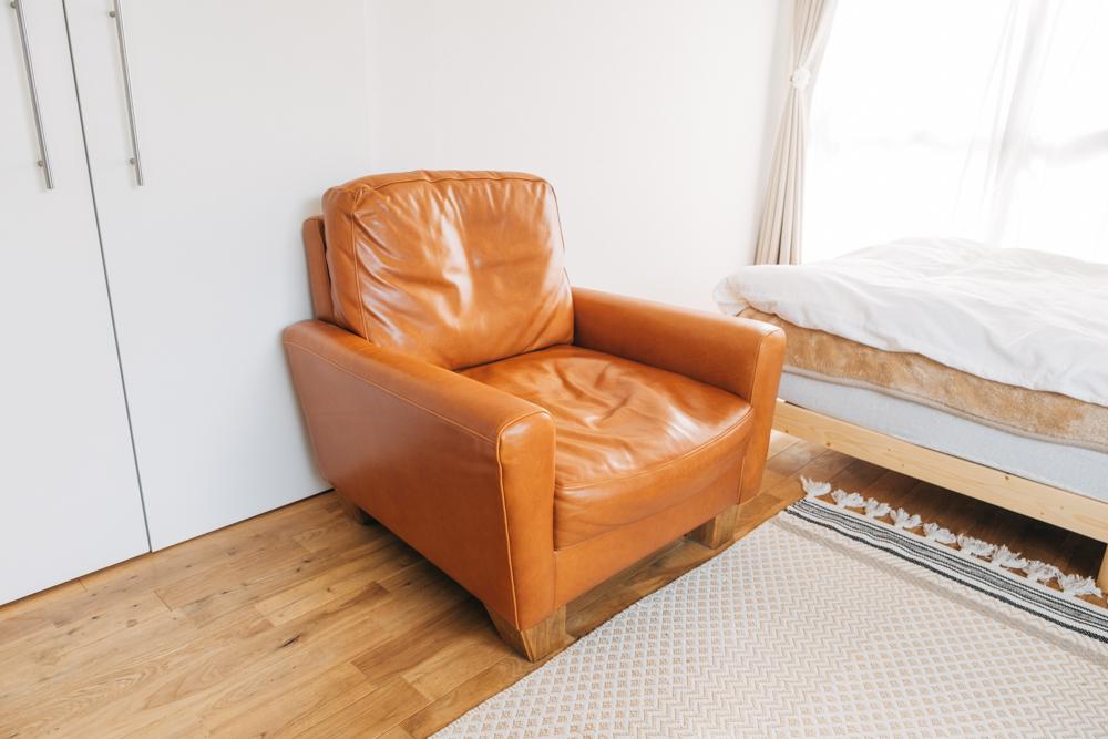テレビを見たり、本を読んだりは対面に位置し、お気に入りだと話す詳細ACME Furnitureのソファに腰掛けて。「ソファはレザーのものが欲しかったのですが、良くあるアメリカンなものだとデザインが強すぎてお部屋に合わないだろうと思い探し回りましたね。今のものはデザインもナチュラルで、サイズ感も1人用でピッタリだったため気に入っています。」