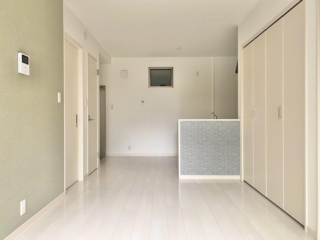 こちらはモスグリーンの壁紙とキッチンのタイルがおしゃれな、築浅のお部屋。