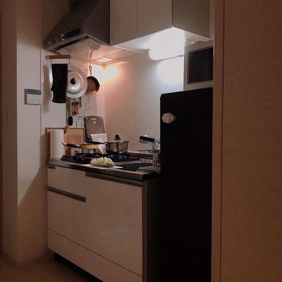 シンプルデザインのコンパクトなキッチン。レンジフードからよく使うツールを吊り下げ、空間を有効活用。