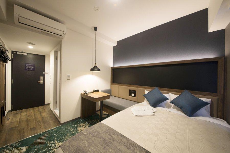大きなダブルベッドでぐっすり眠れそうな室内は、落ち着いたデザインで統一されています。小さなテーブルもあるので、食事をする際などに使えそう。