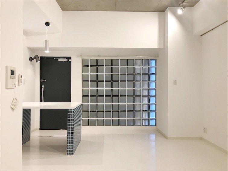 対面式キッチンが自慢の、ゆったりした13.5畳の1K。まっしろな壁と床に、ネイビーのタイル、そしてガラスブロックと、四角形が整列する様子がとても美しいお部屋です。
