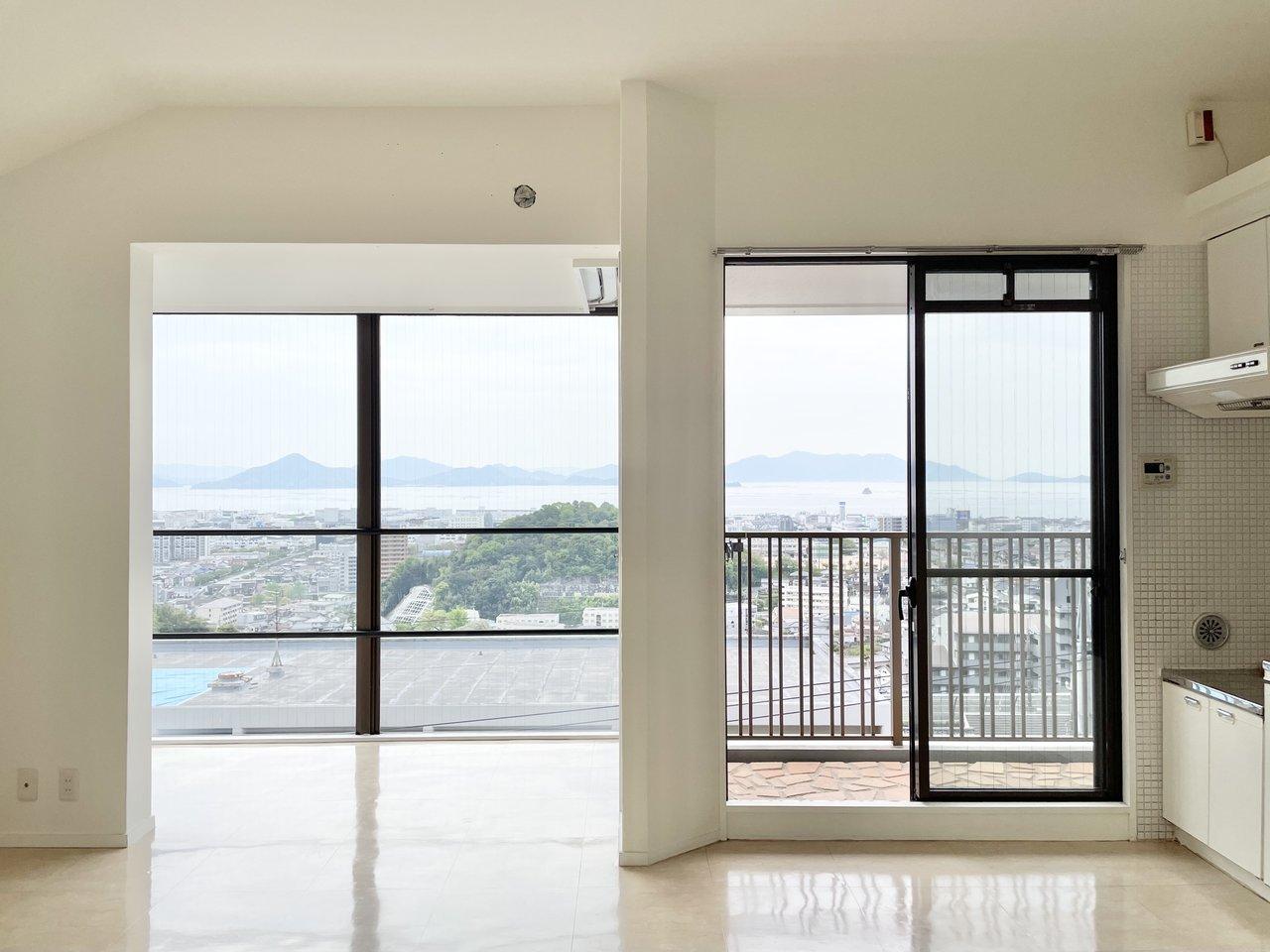 リノベーションで白を基調にしたナチュラルな内装に生まれ変わった2LDK。14畳のリビングに入ると、この眺めが待っています。眺望がいい上に、窓も大きい。まるで別荘に来たかのよう。
