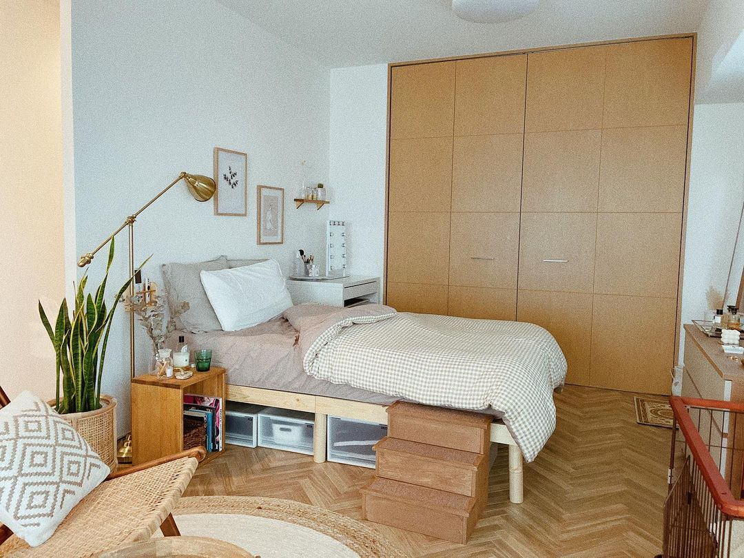 奥まった部分にはベッドを配置。少し高さのあるものにして、下にはスーツケースも入れられ、収納として活用できるよう工夫。