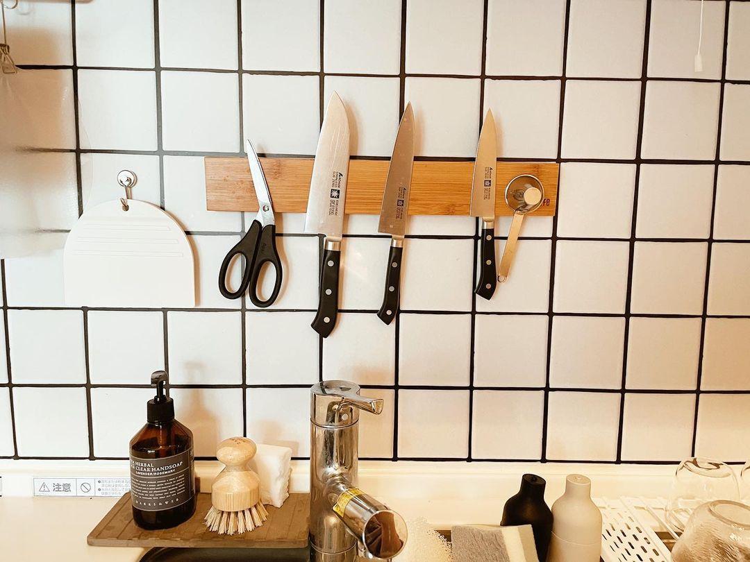 壁のタイル風の壁紙も自分で貼ったもの。さらに、貼って剥がせるテープを使ってナイフラックを設置しました。
