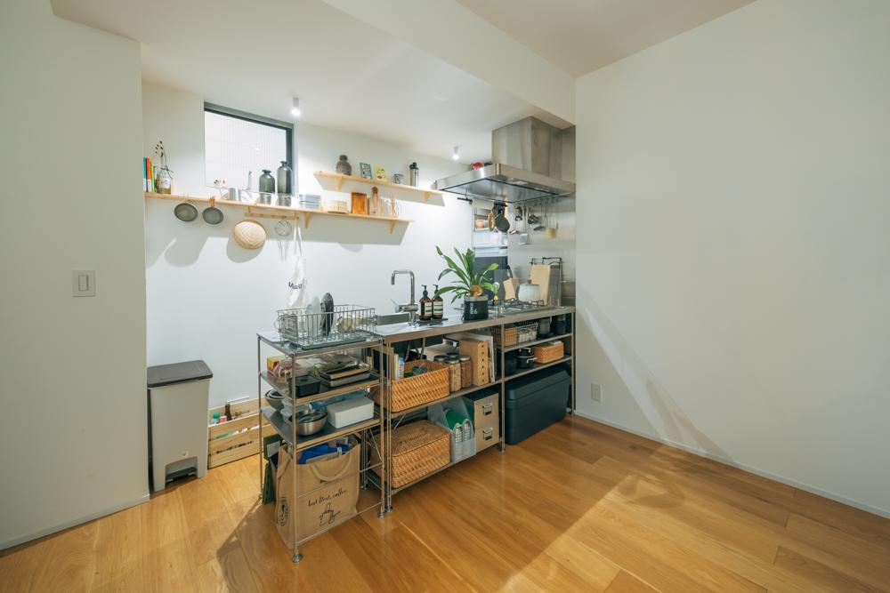 ステンレスユニットシェルフで組み立てられた台所はこだわりのひとつ。 「備え付けのシェルフがmuji+Kitchenなのですが、そこに後付でステンレスユニットシェルフを足すことで二人暮らしに対応できる収納スペースを設けました。」