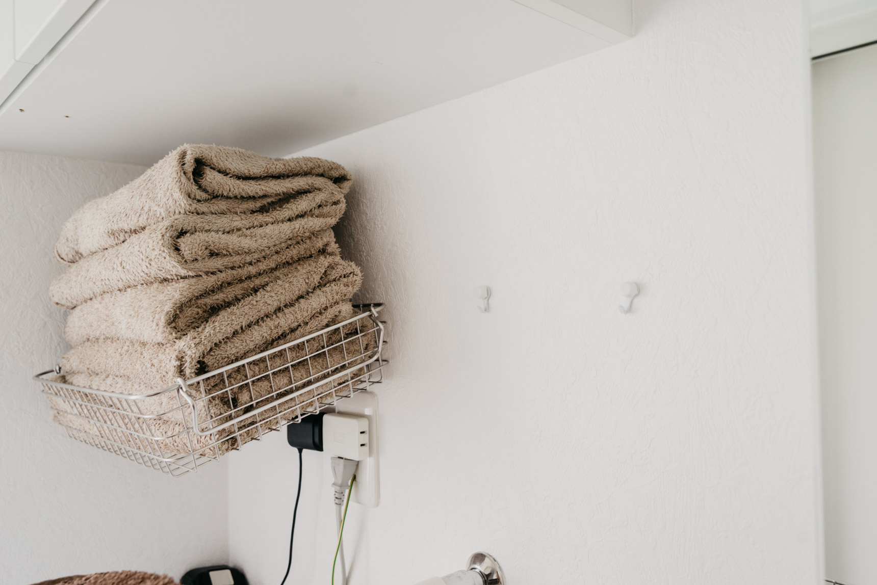 脱衣所のタオルの収納。無印良品のステンレスワイヤーバスケットを、賃貸OKのフックでそのまま壁づけ!シンプルでいろんな場所に活用できそうなアイディアです。