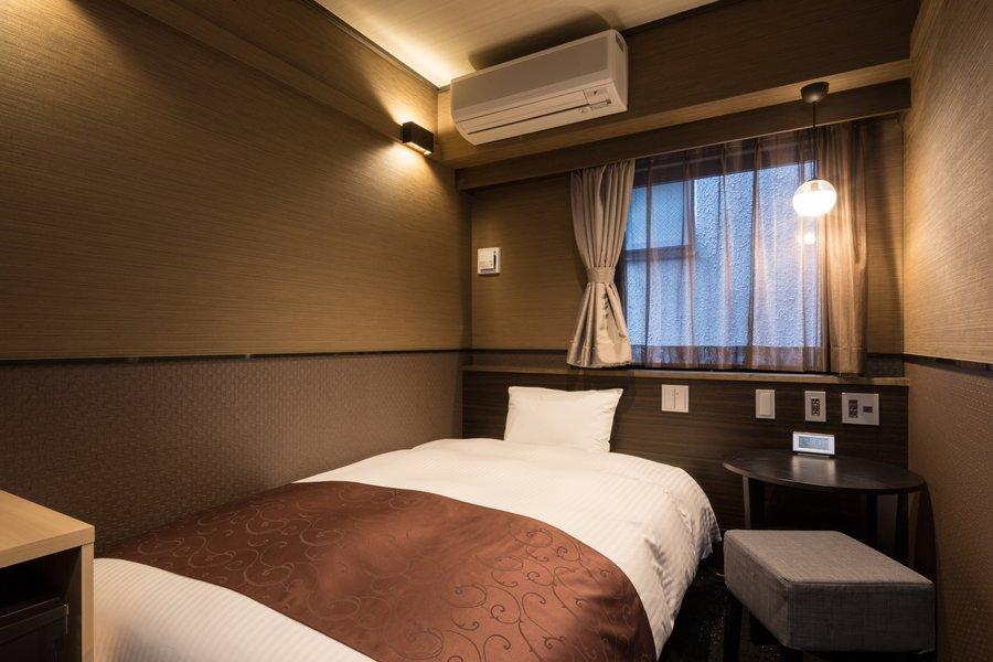 室内は茶を基調とした、シンプルで落ち着いた雰囲気。ベッドは高級ベッドメーカーのシモンズ製のものなので毎日快適にお休みいただけます。ケトルや冷蔵庫、ドライヤーなど、長期滞在するために必要な設備も揃っていますよ。