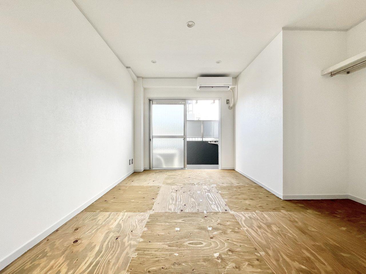 おおぶりの合板がタイルのように敷きつめられたワンルーム。最上階の角部屋です。模様がそれぞれ異なる床と、真っ白な壁の対比が美しく感じられます。