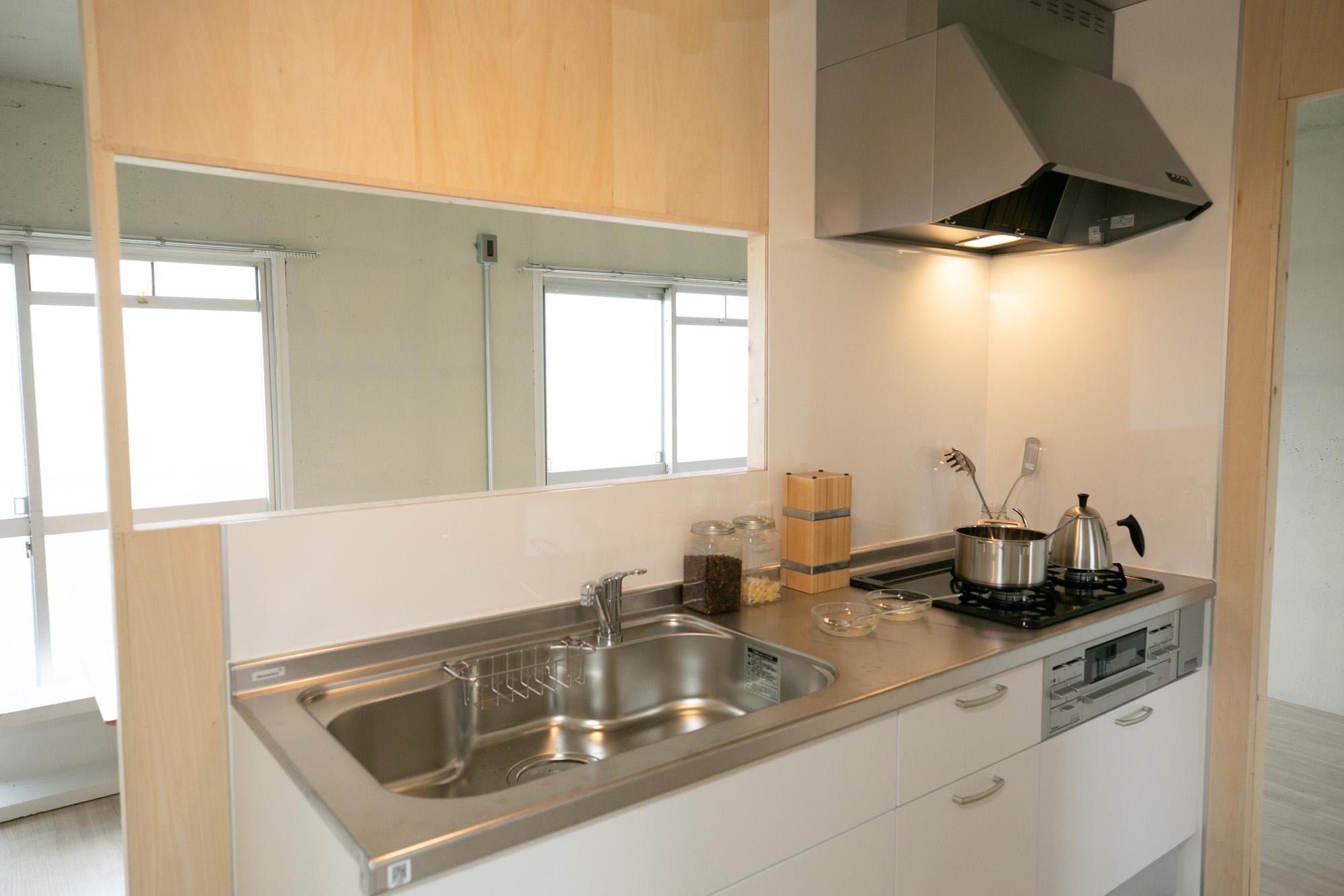 部屋の真ん中に配置されているシステムキッチン。バルコニー側に開口があって、眺めもいいんです。