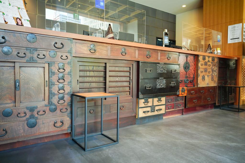 フロントは江戸時代の帳場をイメージして作られています。サイズ違いの箪笥をスタッフ総出で全国から一つ一つ集められたのだそう!
