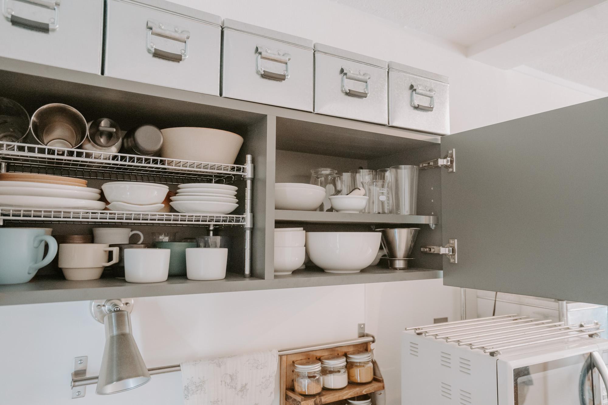 収納ケースを揃えて使うこともポイント。キッチンの吊り戸棚の上には無印良品のトタンボックスが並んでいます。