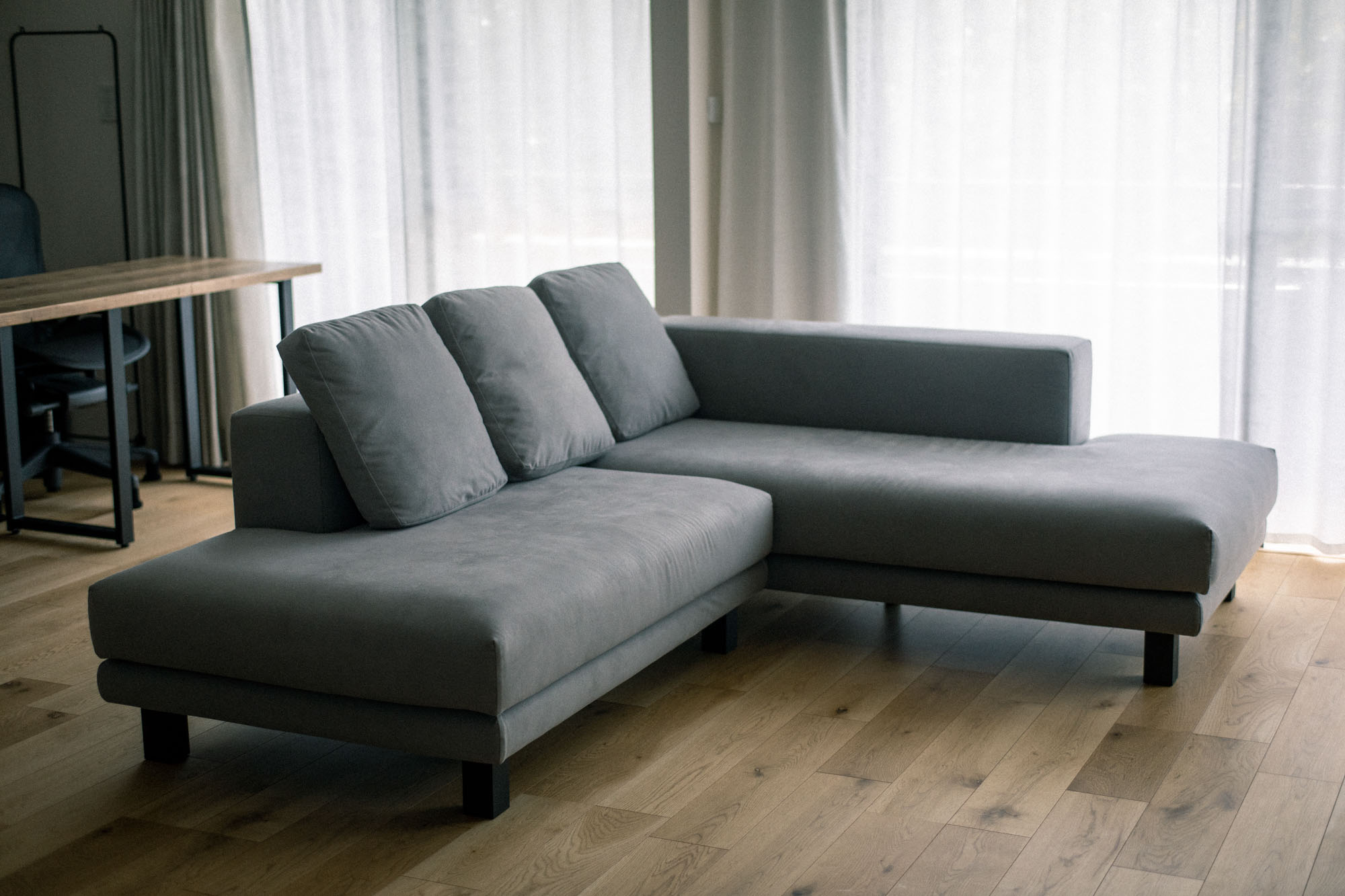 リビングスぺ―スのインテリアを「グレーとダークグレー、無垢の木の色」の3色で整えているとのこと。リビングに置いた大きなL字型のソファは、ソファ専門店の「NOYES」で購入。ワンちゃんが引っ掻いても平気な素材のものを選んだそうです。