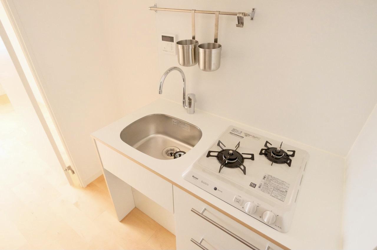 2口コンロで同時調理可能。上部にキッチンツールを掛けられるポールがあり、スペースを余すことなく活用しています。