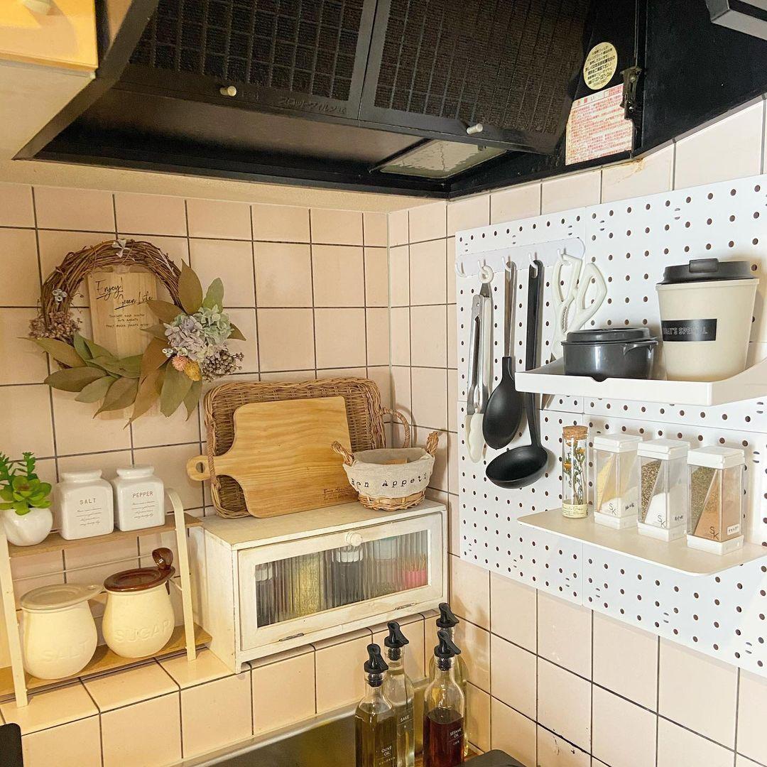 ナチュラル系の収納ラックやケースで統一されている、一人暮らし用のキッチン。壁は100均のダイソーの吸盤でつけられる有孔ボードに、よく使う調理器具などを吊るして収納しています。賃貸でもできる、グッドアイディアです。