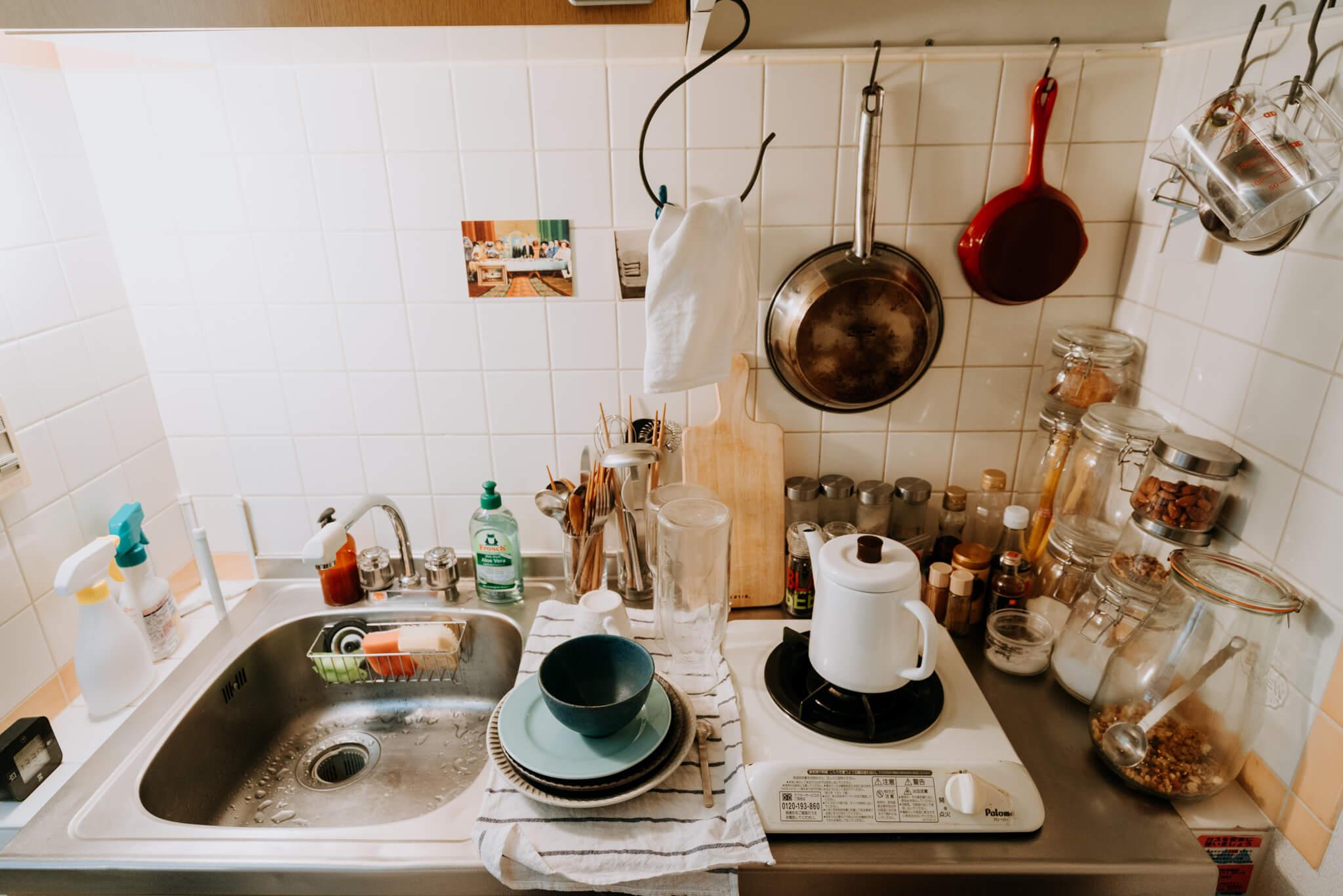 幅のコンパクトな一人暮らし用のキッチンで、上手に収納されている方の事例。砂糖や塩だけでなく、ナッツやグラノーラを瓶に詰めて収納。瓶の天井部が平らなので、上に重ねて収納できるところもポイントです。