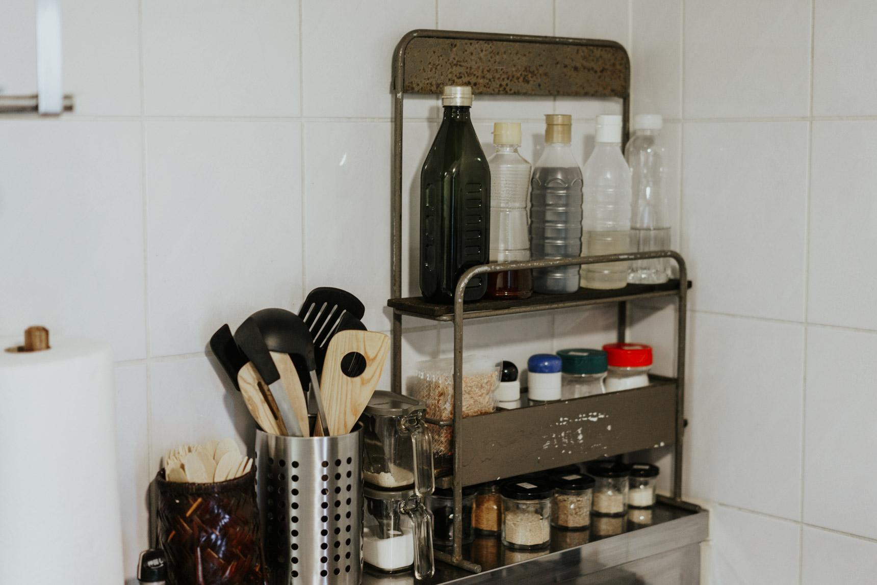 コンロ周りに段になった場所があり、調理器具やスパイスラックを置いています。アンティークショップで見つけたという棚がシンデレラフィットしていますね。お部屋のなかにも古道具が多いので、キッチンだけギャップが生まれることがありません。好きな見た目のものに収納するだけで、料理のモチベーションも上がりそうです。