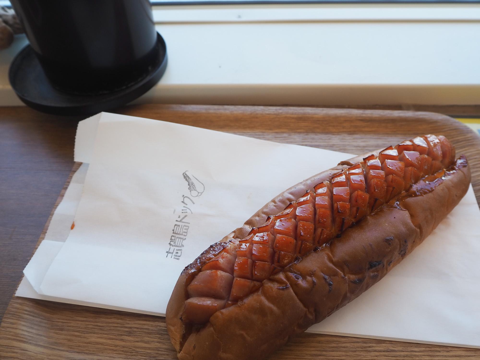 看板メニューの「志賀島ドッグ500円(税込)」をチョイス。カリっと焼かれたパンに熟成させたソーセージとキャベツ、オーロラソースがオン。