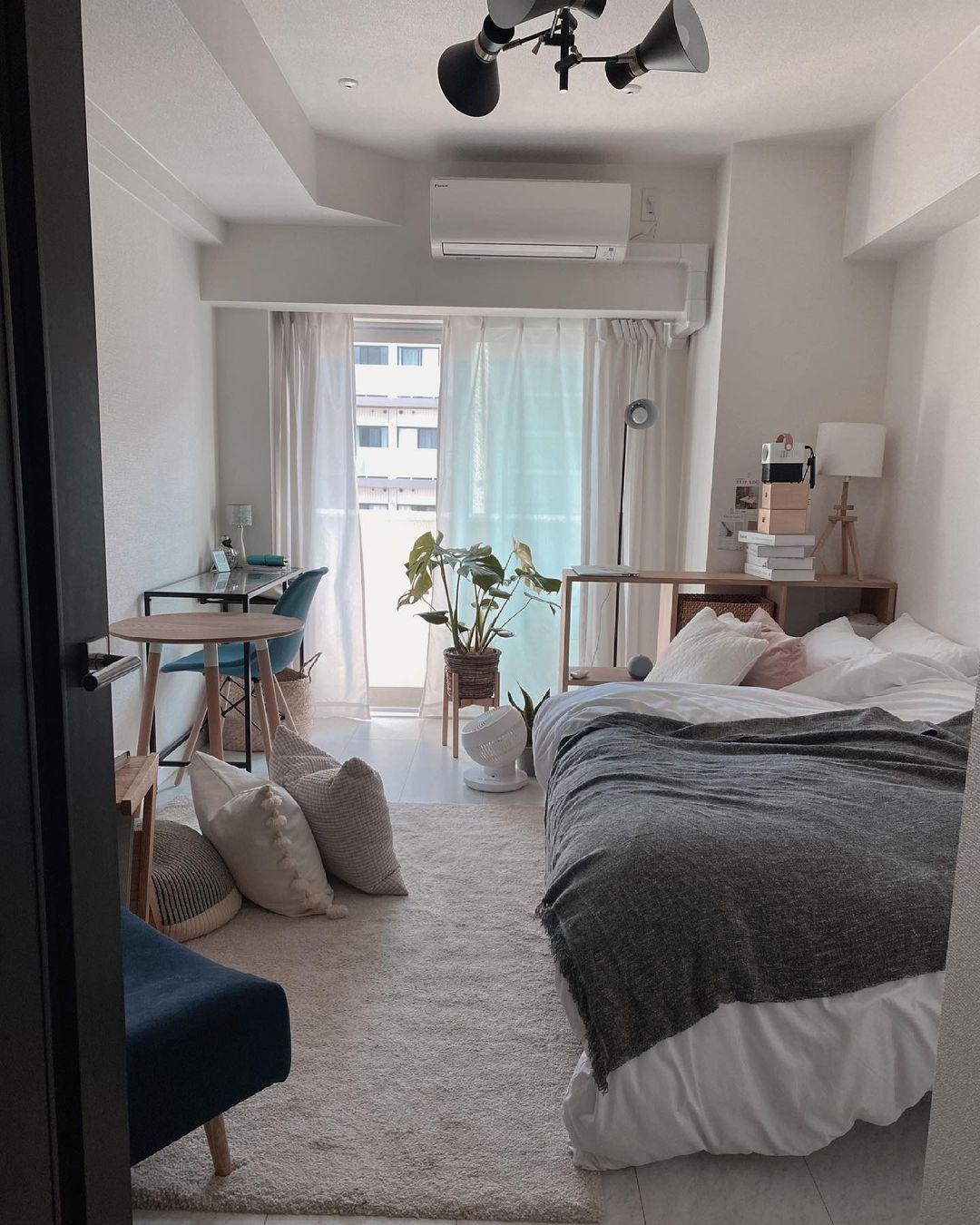 縦長の7.6畳、手前にセミダブルベッドを配置し、一人がけのソファ、丸テーブル、窓際にはデスクと収納と、うまく配置していらっしゃいます。